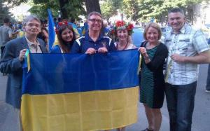 Canadian MP Peggy Nash (right) with Canadian MPs Ted Opitz (centre) and James Bezan (far right) in Kharkiv, while pro-Ukrainian rally just passed by
